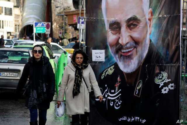 Women walk past a banner of Iranian Revolutionary Guard Gen. Qassem Soleimani, who was killed in Iraq in a U.S. drone attack on…