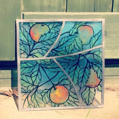 Hand-painted stained glass panel of apples and leaves