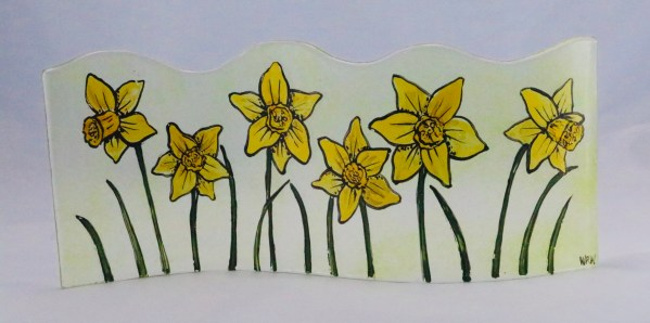 Long curved handpainted fused glass panel with daffodils on transparent spring green background