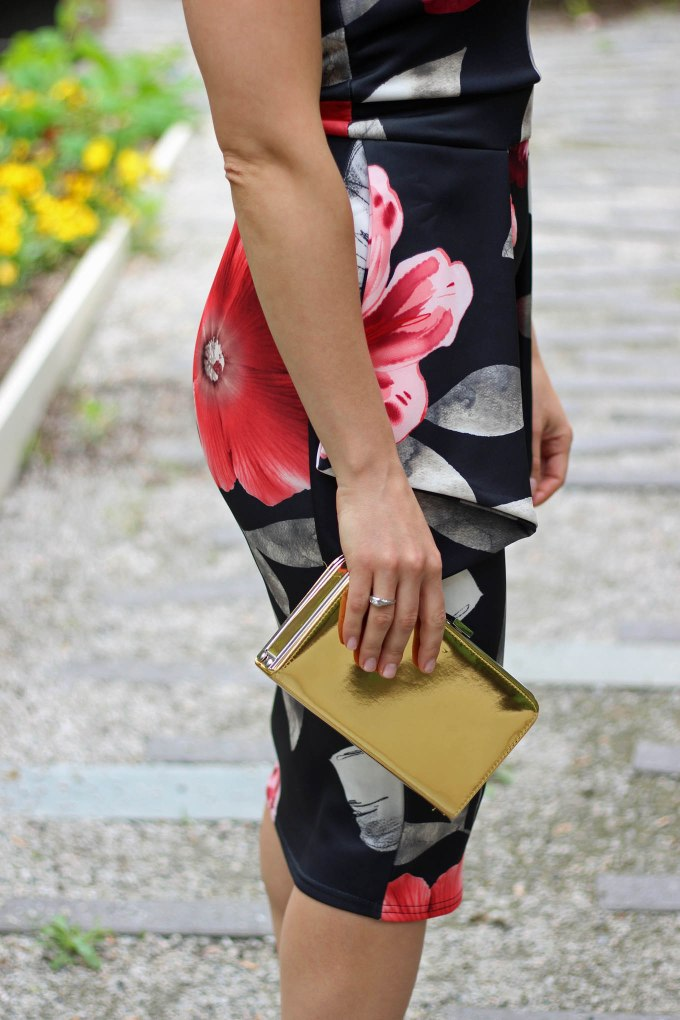 Lifestyle Blogger Roxanne of Glass of Glam wearing a floral Boohoo dress and gold box clutch