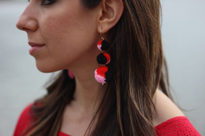 Lifestyle blogger Roxanne of Glass of Glam wearing a red Cuddy Studios top, Baublebar earrings, and Old Navy Denim