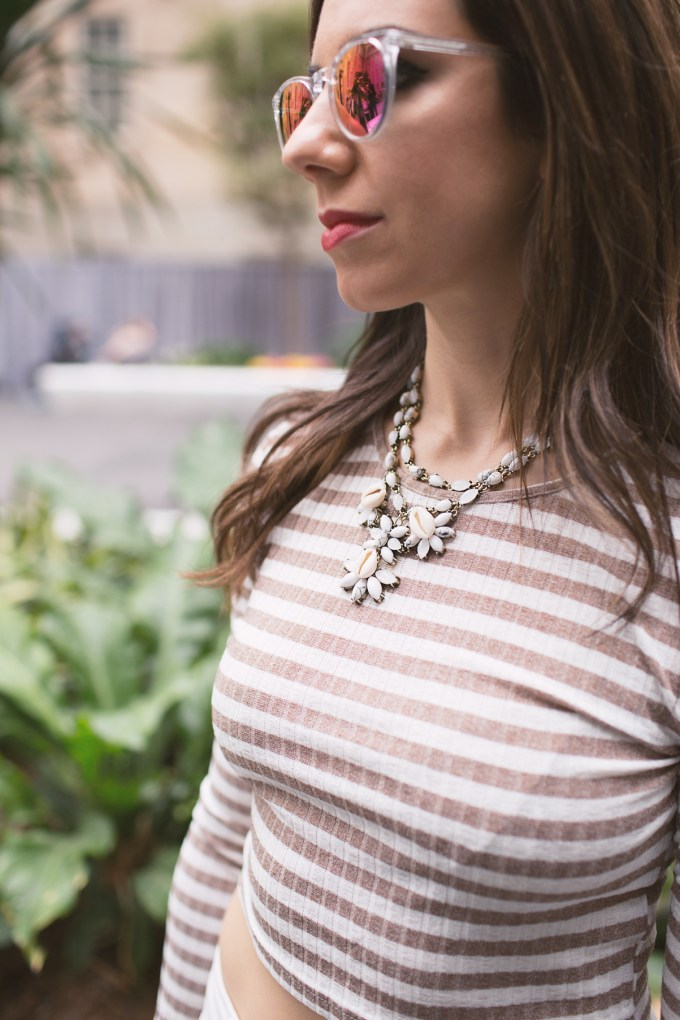 Lifestyle blogger Roxanne of Glass of Glam wearing a striped crop top, Old Navy denim, a baublebar necklace, and warby parker sunglasses