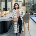 Lifestyle blogger Roxanne of Glass of Glam wearing a windowpane duster coat, velvet bodysuit, distressed denim, and a Gucci soho disco bag