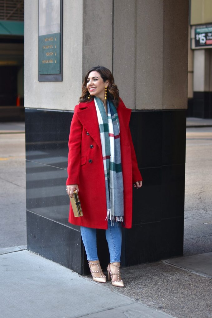Lifestyle blogger Roxanne of Glass of Glam wearing a red ASOS coat, Valentino rockstud heels, a plaid scarf, and Madewell denim
