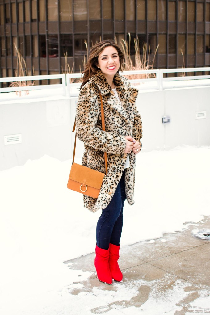 Lifestyle blogger Roxanne of Glass of Glam wearing a white lace Shein top, leopard coat, Mott and Bow denim, and red booties.