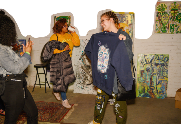 People holding clothing they have designed