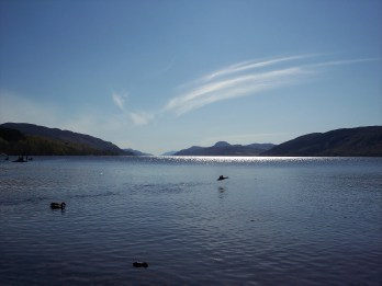 Ducks taking flight above a shimmering Loch Ness