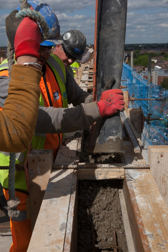 Concrete being poured in parapet wall