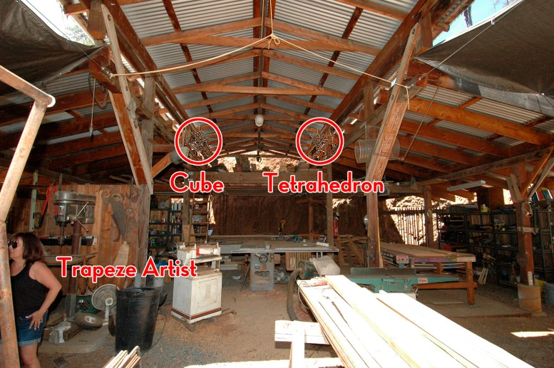 """Photo of a workshop with a pole barn roof and various wood and metal machines. From the ceiling hang welded steel sculptures in the forms of articulated or """"Disguised"""" Tetrahedron and Cube."""