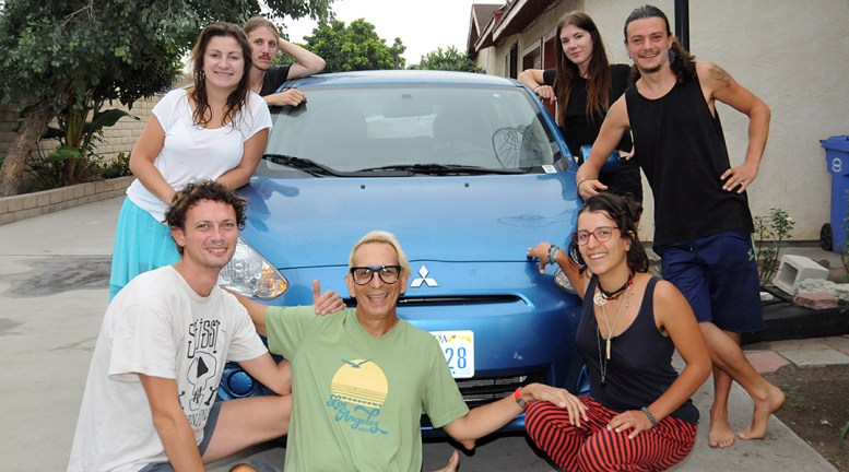photo of 7 people grouped around a compact car