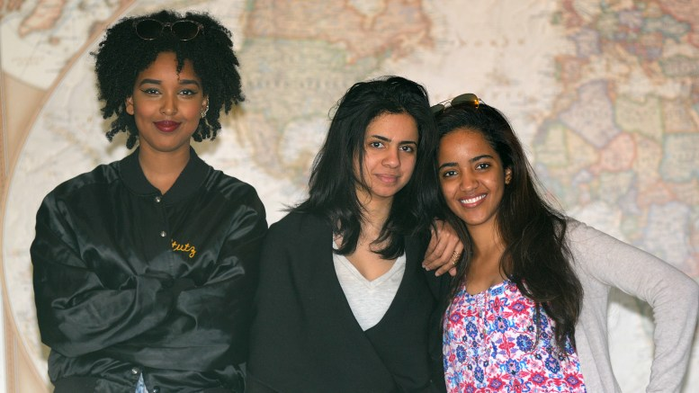 Hana, Shahad & Aisha stand in front of a large world map