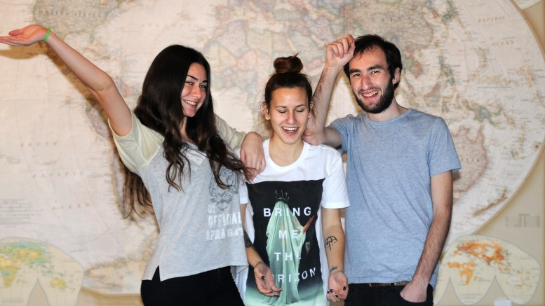 Mariam, Maya & George stand in front of a large world map