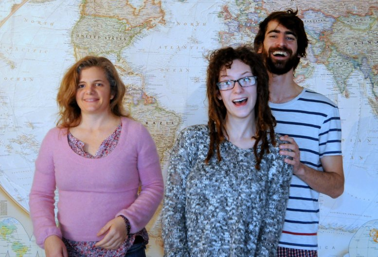 Julia, Rachel & Simon standing in front of a map of the world