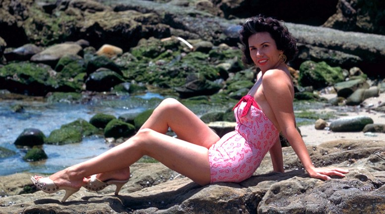 Vintage photo of Sheila Zucman wearing a 1-piece swimsuit and reclining on the rocks at Laguna Beach, California