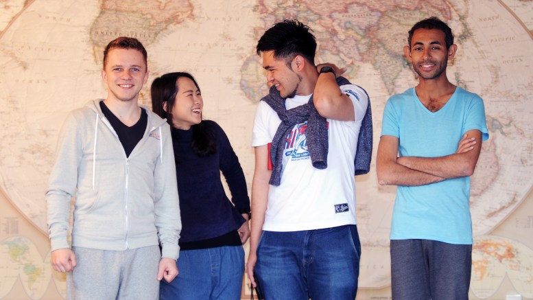 Maksym Lysak, Yu-Hsin Weng, Cheyuan Li & Ahmed Seddik  standing in front of  a large world map