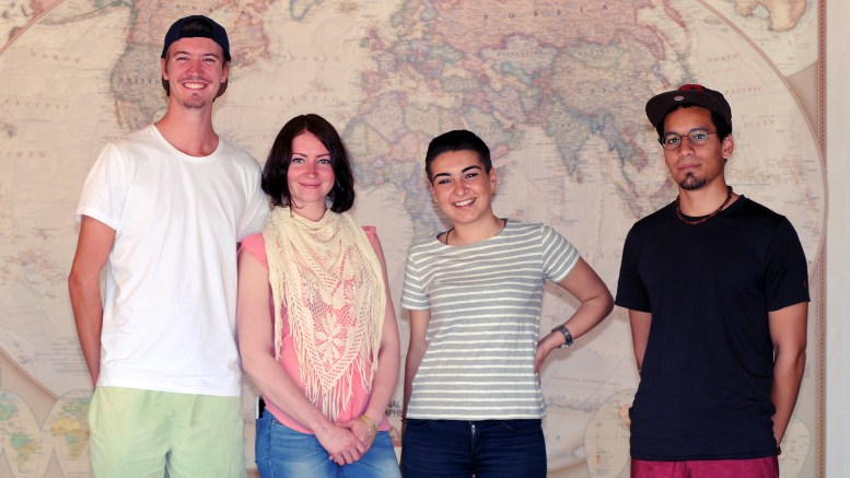 4 people standing in front of a large world map