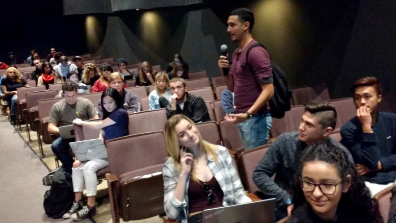 CSULB student holding a microphone and addressing the class in the University Theater