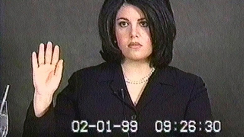 Video frame of Monica Lewinsky raising her hand to be sworn in for testimony. The frame has the date 02-01-99 burned into it.