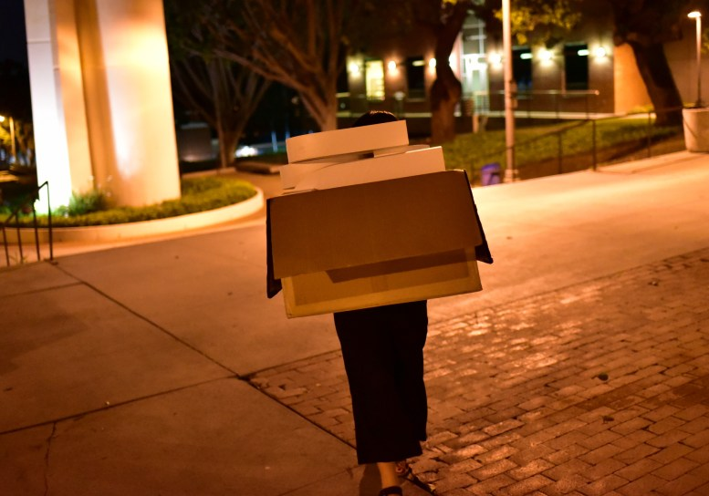 """TEDxCSULB curator Camille Raquel carries a box with the """"T-E-D-x-C-S-U-L-B"""" letters across the CSULB campus at night. You can't actually see her face in this photo, the large box of letters covers it - you only see a box and legs"""