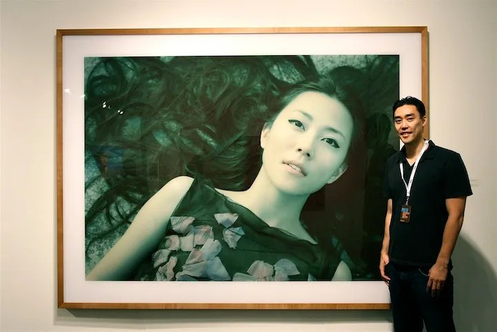 "Image of a young man standing in front of a large wall mounted photograph from Izima Kaoru's series ""Landscapes with a Corpse"""