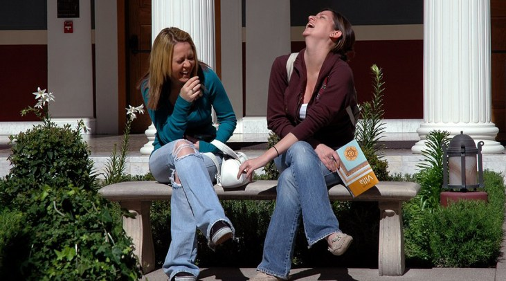 CSULB Students sitting on a bench and laughing at The Getty Villa in Malibu, CA