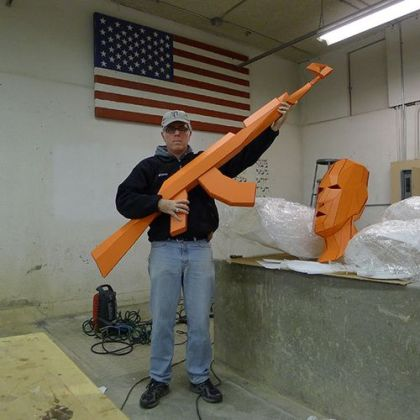 Joseph DeLappe holding an oversized rifle made out of cardboard polygons from the game America's Army