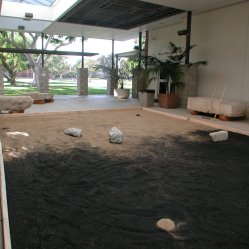 "Photo of Glenn Zucman's ""Zen Entropy Garden"" (a large ""zen garden"" / sandbox with half white sand, and half black sand, and rakes that let visitors create their own zen garden configurations as they also mix the sand into an entropic grey) installed in the CSULB School of Art, Art Gallery Courtyard"