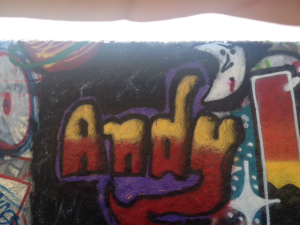 "the word ""Andy"" painted in yellow and red and with a black outline"