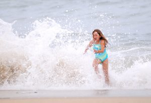a young girl runs from a crashing wave at Seal Beach, CA