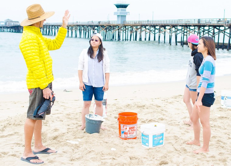 4 CSULB students & faculty stand on the beach at the Seal Beach Pier. It's a cold day in June and they're dressed in shorts & sweatshirts.