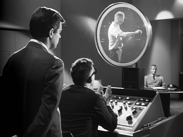 B&W screen cap of an Outer Limits episode from 1963 featuring 2 men viewing another man's life on a circular video screen