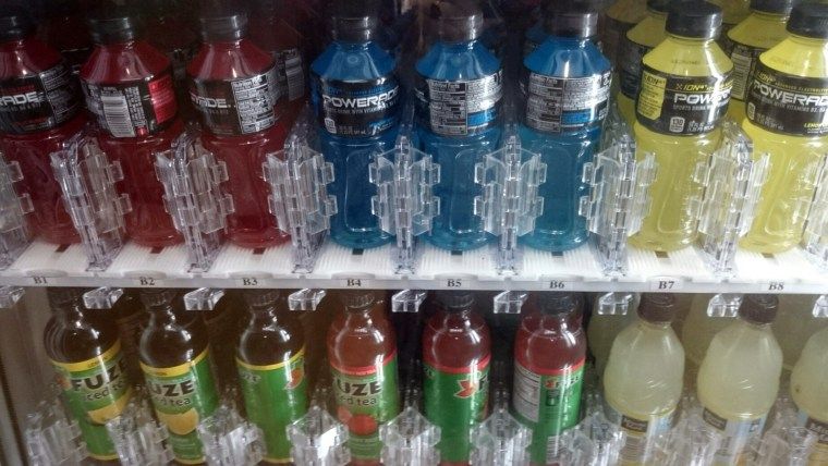 close photo of inside a drink vending machine showing rows of sports drinks in different colors: red, blue, yellow