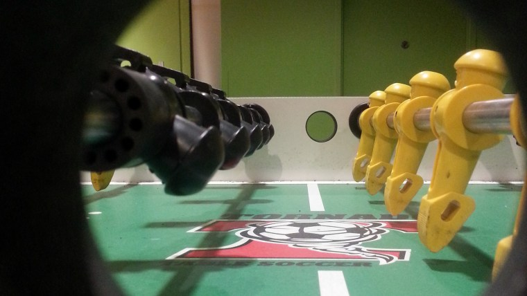 "Photo of a Foosball table with the camera lens in the midfield hole for dropping the ball, so the feeling is of a ""player level view"" of the field"