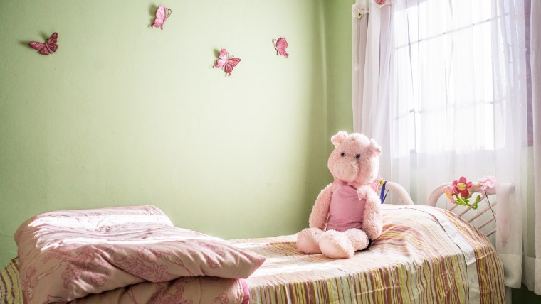 Image of a young girl's room, with a pink bear sitting on the bed