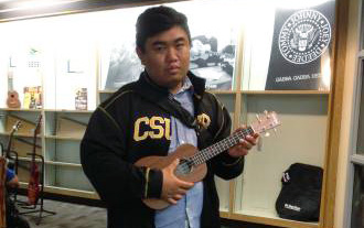 Justin Marquez playing the ukulele in the CSULB Bookstore Guitar Store