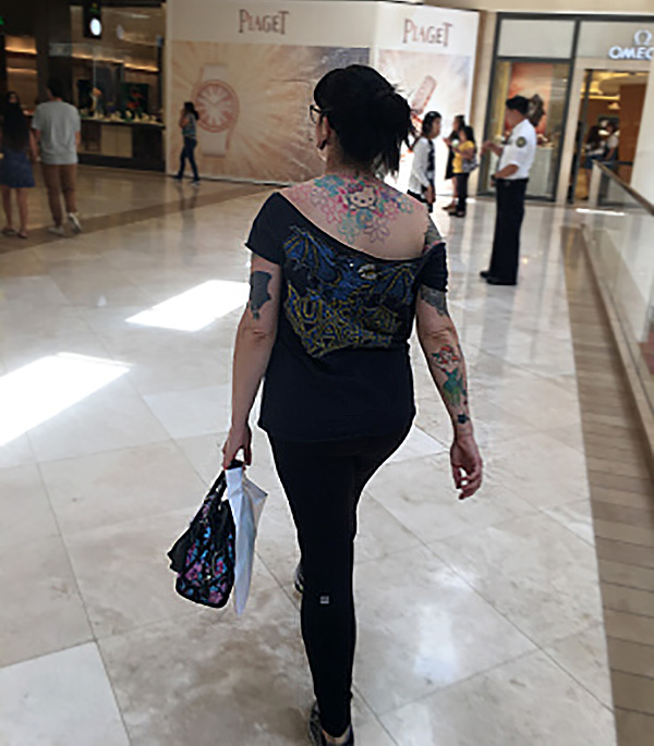 a woman with a lot of tattoos and dressed in black walking through a mall