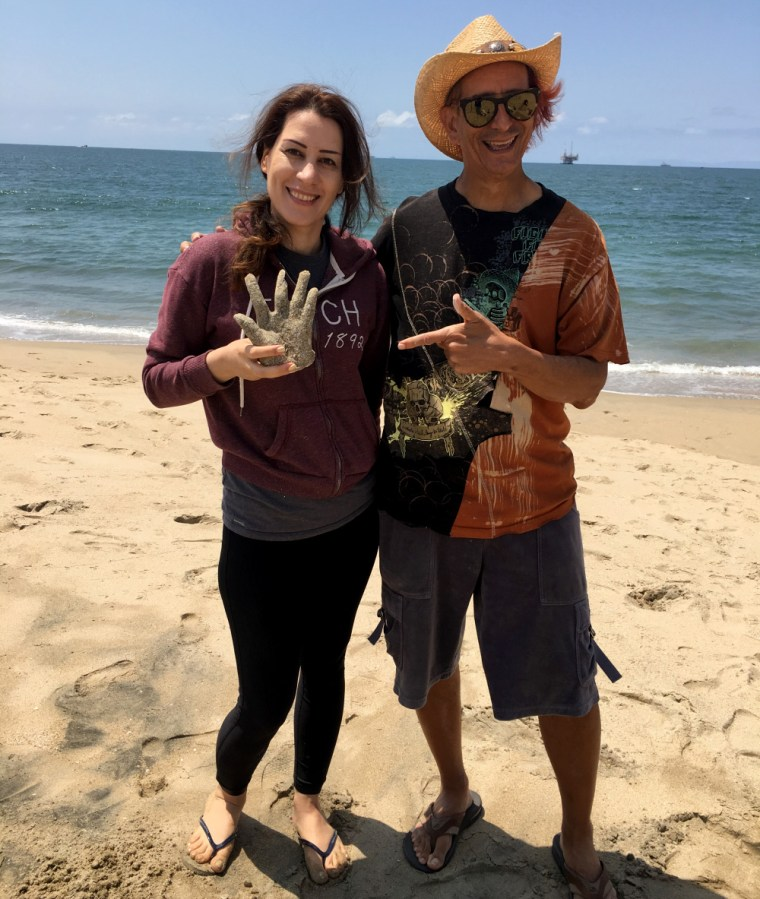 Rannah Jahedi & Glenn Zucman at the Seal Beach Pier. Rannah holds a plaster casting of her hand which Glenn points to. Sun, sand, the Pacific Ocean, and blue sky is behind them.