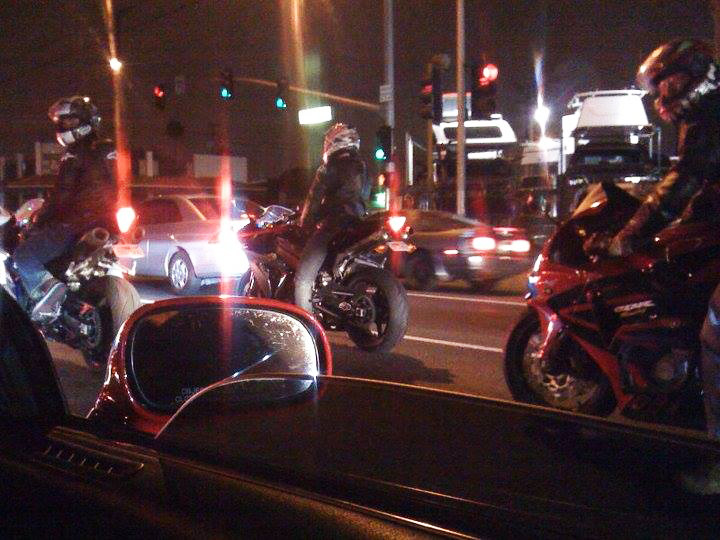 motorcycles riding down the street at night as shot out a car window