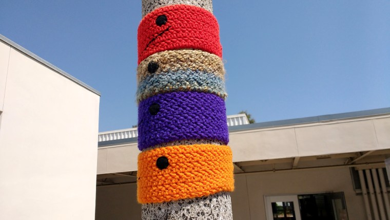 """4 """"collars"""" in red, brown, purple, and orange yarn are woven around a light pole at the CSULB, College of the Arts, School of Art, near the Art Gallery Complex"""