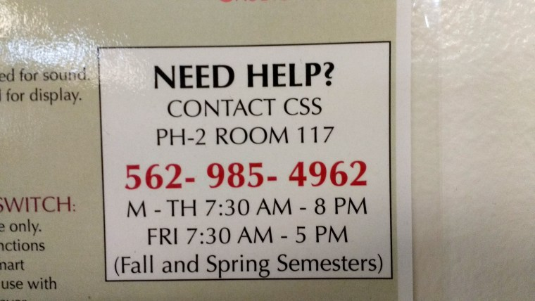 "photo of a ""need help?"" sign next to the projection ""smart panel"" in classroom FA4-311 in the School of Art at CSULB"