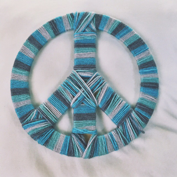 peace symbol made of different shades of blue yarn