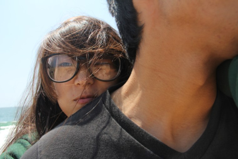 Lydia Chang at the Seal Beach Pier with her head resting on her boyfriend's shoulder