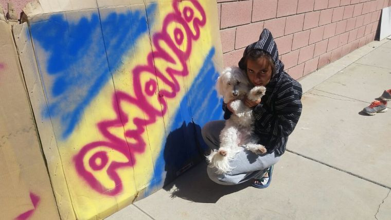 "Amanda Martinez and her dog Tofu in front of the name ""Amanda"" painted in bubble letters on a large sheet of cardboard"