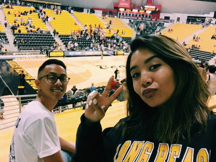 Brian Sath & Maritess Inieto smile at the camera as a Long Beach State vs Washington State women's volleyball match goes on behind them inside The Pyramid at Long Beach State University