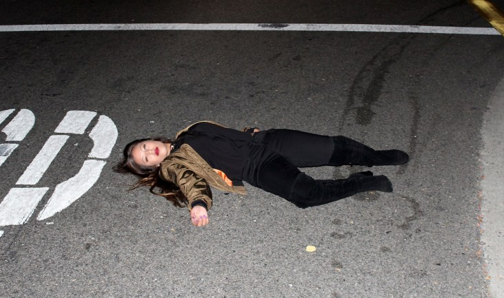 Briana Garcia lying in the street, near a stop sign, at night, as though she'd been hit by a car