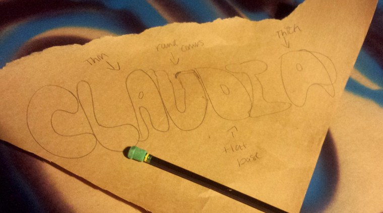 "a sketch on brown craft paper of Claudia Sanchez' name ""Claudia"" in bubble letters"