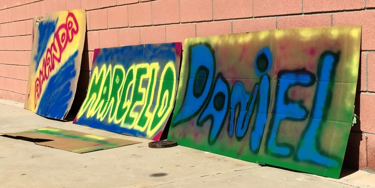 "3 large sheets of cardboard with the spray painted names ""Amanda, Marcelo, Daniel"""
