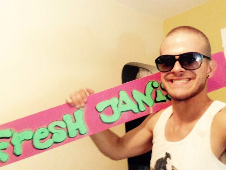 "Janis Vernier holding the words ""Fresh Janis"" painted in Green on Pink on a long narrow board"