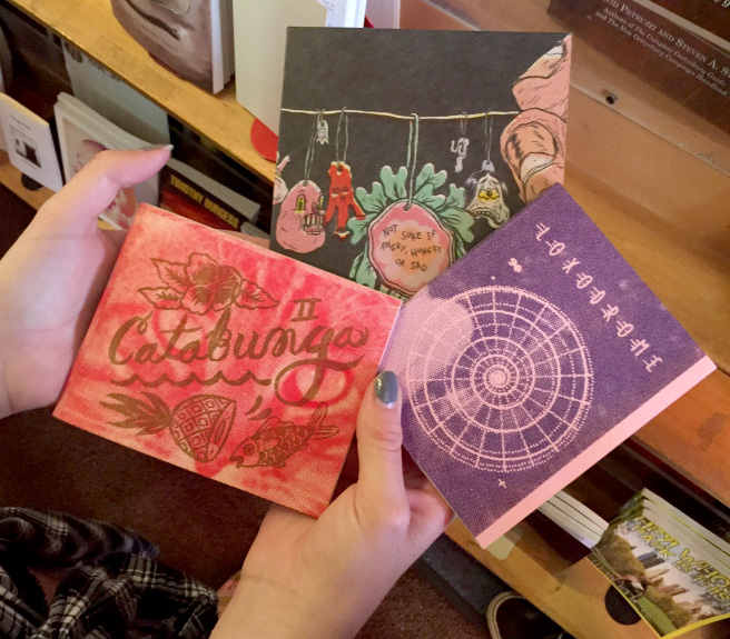 hands holding several zines at the zine rack at Small World Books in Venice, CA