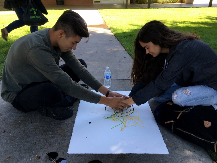 sitting on the sidewalk on the CSULB campus and making a tandem pastel drawing